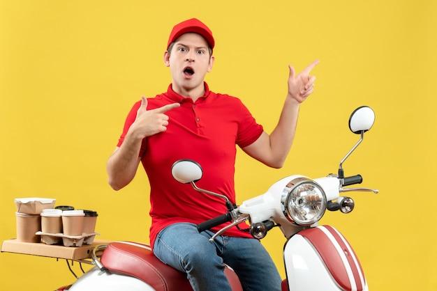 黄色の背景に上向きの注文を配信する赤いブラウスと帽子を身に着けている不思議な若い男の正面図