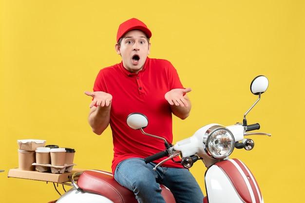 黄色の背景に注文を配信する赤いブラウスを着ている不思議な若い男の正面図