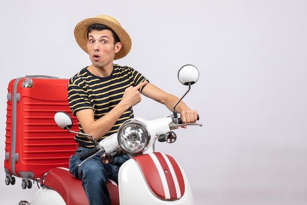 白い背景を指している原付の麦わら帽子と不思議な若い男の正面図