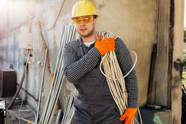 ロープを運ぶヘルメットをかぶった労働者の正面図