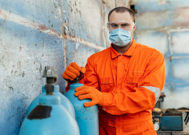 Вид спереди работника в защитных очках и медицинской маске