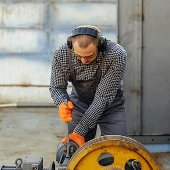 保護手袋とヘッドホンを着用した作業者の正面図
