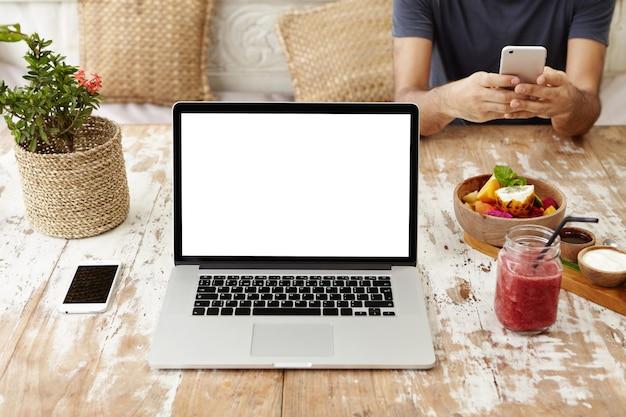 Вид спереди на рабочее место самозанятой женщины или фрилансера: универсальный портативный компьютер, опирающийся на деревянный стол со смартфоном