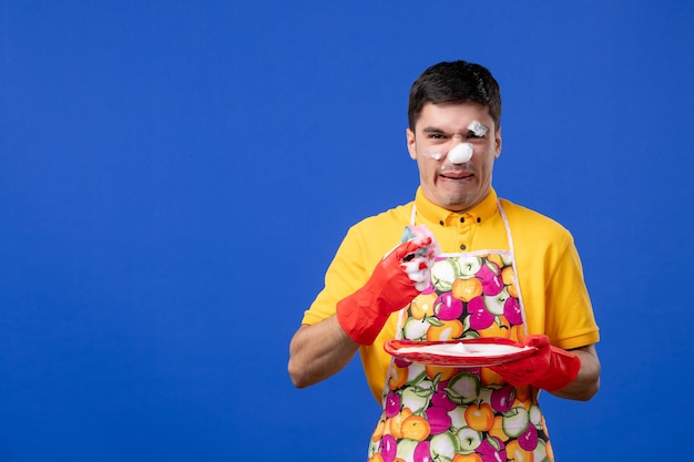 青い壁の彼の顔の洗浄プレートに泡で心配している家政婦の正面図