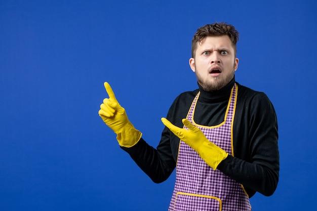 Вид спереди обеспокоенной домработницы в черном свитере, стоящей на синей изолированной стене