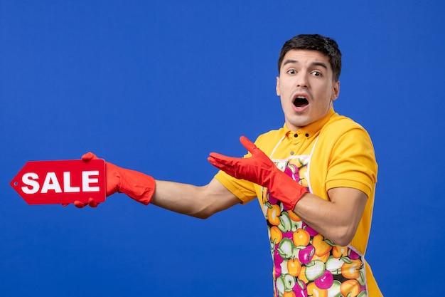 파란색 외진 벽에 판매 표지판을 들고 있는 노란색 티셔츠를 입은 걱정스러운 남성 가사도우미의 전면