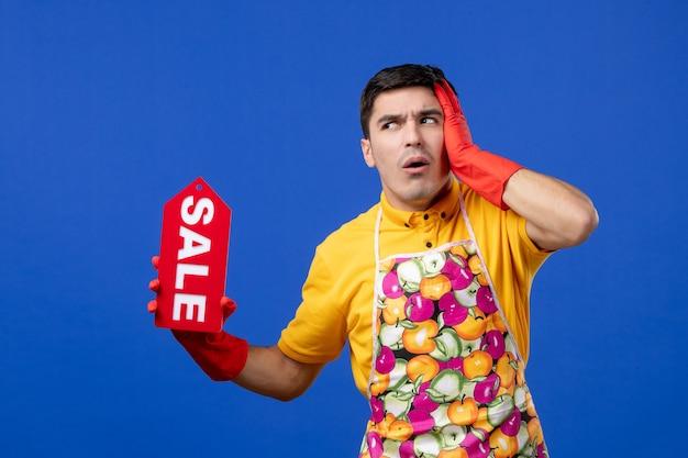 파란색 벽에 판매 표지판을 들고 있는 노란색 티셔츠를 입은 걱정스러운 남성 가사도우미의 전면 모습