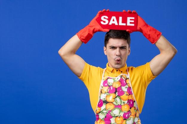 파란색 벽에 머리 위로 판매 표지판을 올리는 노란색 티셔츠를 입은 걱정스러운 남성 가정부의 전면