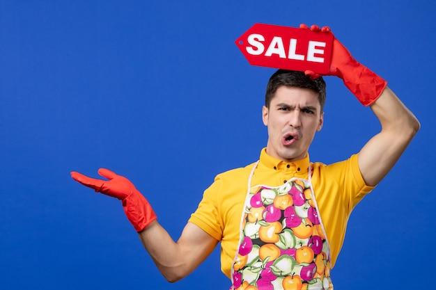 파란색 벽에 머리 위로 판매 표지판을 올리는 무언가를 가리키는 걱정스러운 남성 가정부의 전면