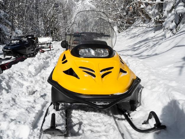 冬の晴れた日の雪の上の黄色と黒のスノーモービルの正面図