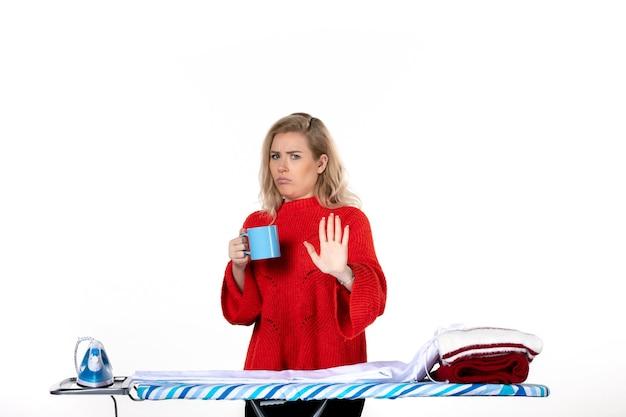 흰색 배경에 파란색 컵을 들고 다림판 뒤에 서 있는 겁 많은 매력적인 젊은 여성의 전면 모습