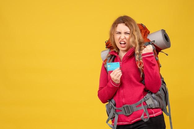 銀行カードを保持している医療マスクの若い野心的な旅行の女の子の正面図