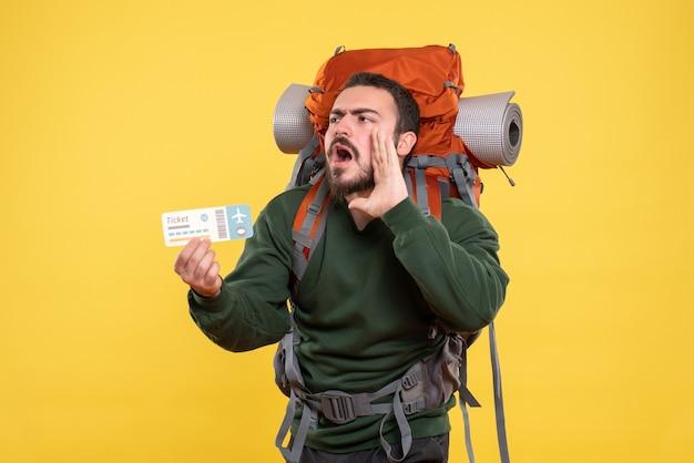 バックパックを持ち、黄色の背景に誰かを呼び出すチケットを持っている若い怒っている旅行男の正面図