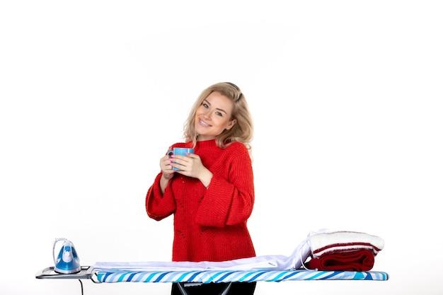 흰색 바탕에 파란색 컵을 들고 다림판 뒤에 서 있는 매력적인 젊은 여성의 전면 모습