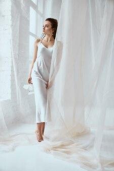 Вид спереди молодой красивой женщины брюнет стоя и держа цветок лилии. портрет девушки с мокрыми волосами, позирующими на белом фоне и смотрящими в окно между тюлем. понятие красоты.