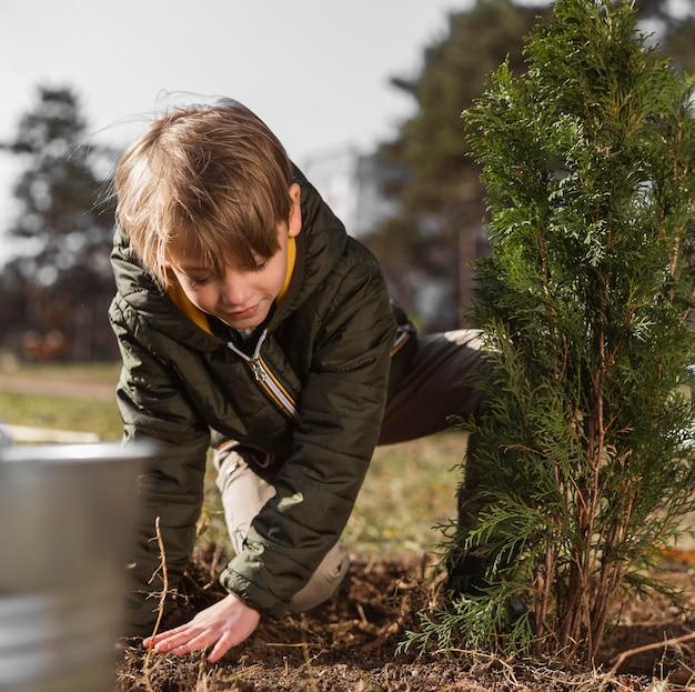 屋外で木を植える少年の正面図