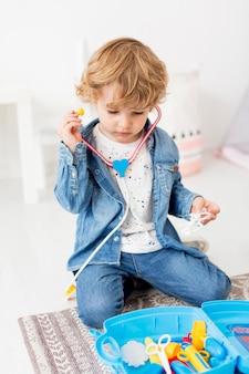 聴診器で遊ぶ少年の正面図