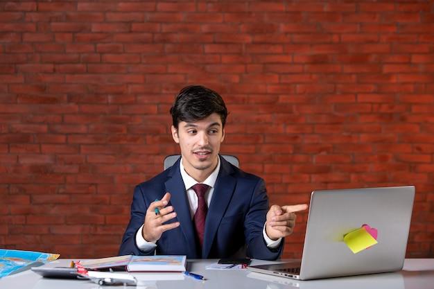スーツの仕事計画請負業者の職業企業プロジェクトビジネスジョブビルダーでラップトップを持って彼の職場の後ろに座っている青年実業家の正面図