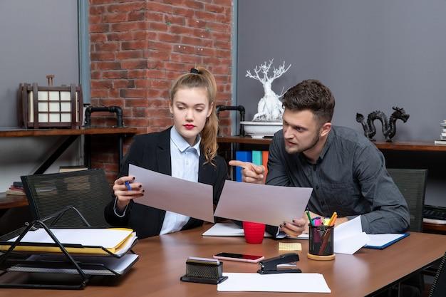 Вид спереди молодых занятых и сбитых с толку канцелярских служащих, обсуждающих одну проблему в документах в офисе