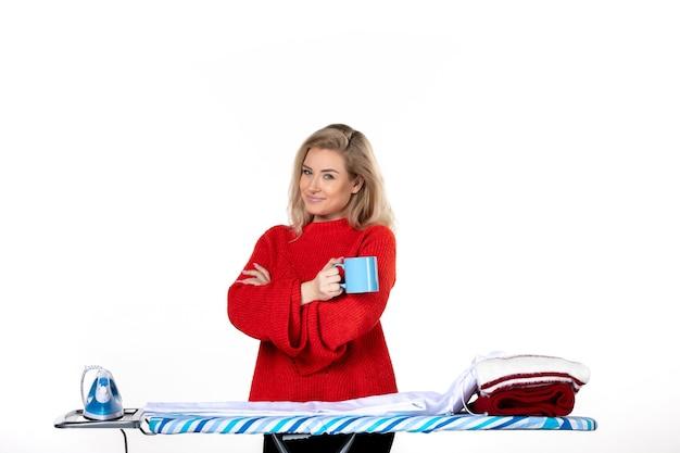 흰색 배경에 파란색 컵을 들고 다림판 뒤에 서 있는 자신감 있는 젊은 여성의 전면 모습