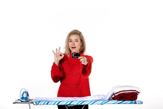 흰색 배경에 안경 제스처를 만드는 은행 카드를 보여주는 다리미판 뒤에 서 있는 자신감 있는 젊은 여성의 전면