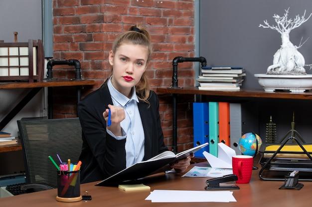 책상에 앉아 사무실에서 문서를 들고 있는 자신감 있는 젊은 여성 조수의 전면