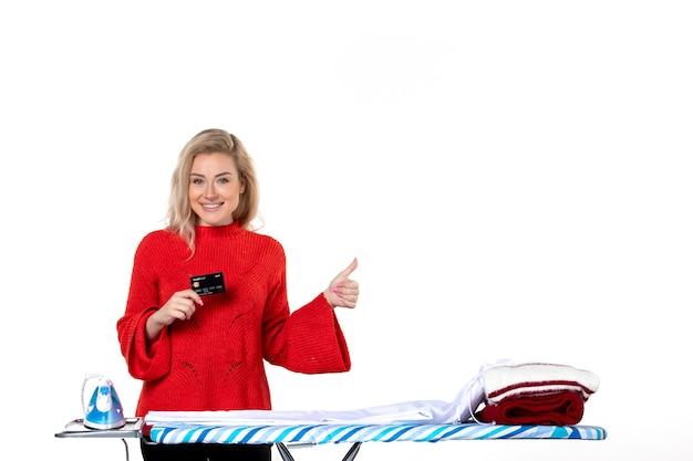 흰색 바탕에 확인 제스처를 하는 은행 카드를 보여주는 다리미판 뒤에 서 있는 자신감 있는 젊은 미소 매력적인 여성의 전면 모습