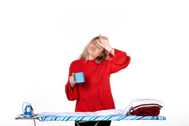 흰색 배경에 파란색 컵을 들고 다림판 뒤에 서 있는 혼란스러운 젊은 여성의 전면 모습