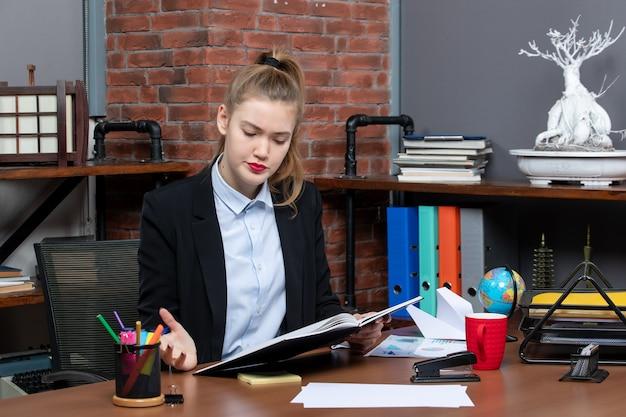 책상에 앉아 문서를 들고 있는 혼란스러운 젊은 여성 조수의 전면