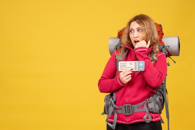 チケットを保持し、上向きの医療マスクで若い混乱した旅行の女の子の正面図