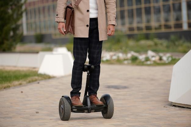 자이로 스코프에 서서 아침에 비즈니스 센터로 이동하는 가죽 가방을 가진 젊은 현대 우아한 남자의 전면보기
