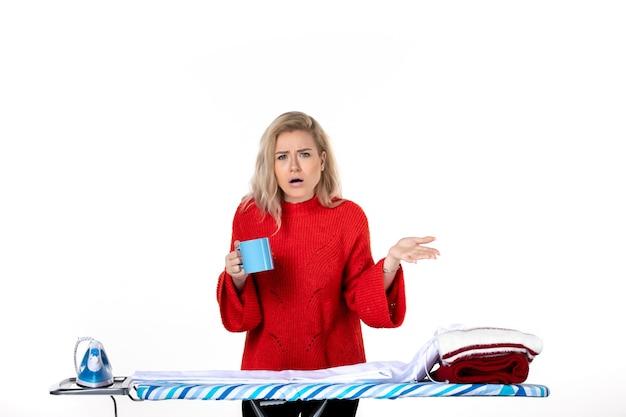 흰색 배경에 파란색 컵을 들고 다림판 뒤에 서 있는 호기심 많은 매력적인 젊은 여성의 전면