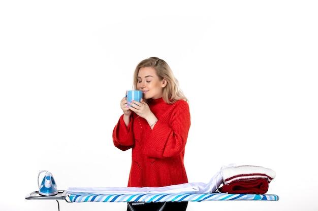 흰색 바탕에 파란색 컵을 들고 다림판 뒤에 서 있는 꿈꾸는 매력적인 젊은 여성의 전면
