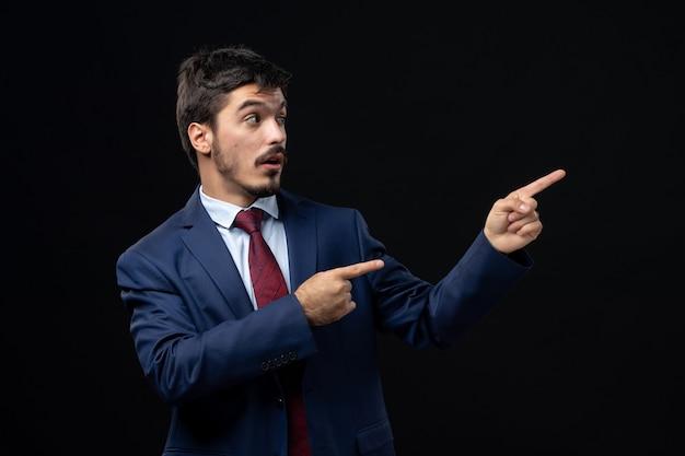 Вид спереди молодого эмоционального сконцентрированного человека в костюме, указывающего вверх на изолированной темной стене
