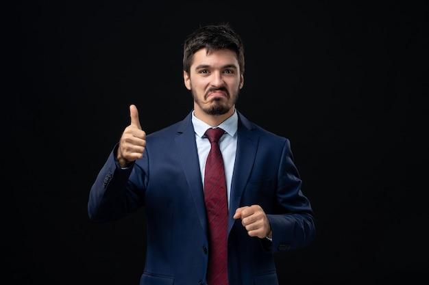 孤立した暗い壁でokジェスチャーを作るスーツの若い感情的な笑顔の男の正面図