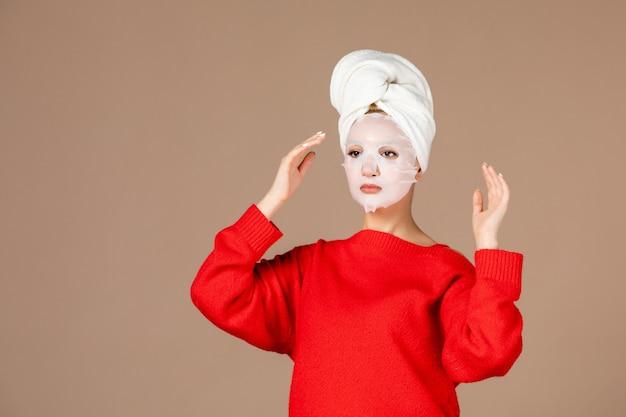 茶色の壁にフェイスマスクを適用する若い女性の正面図