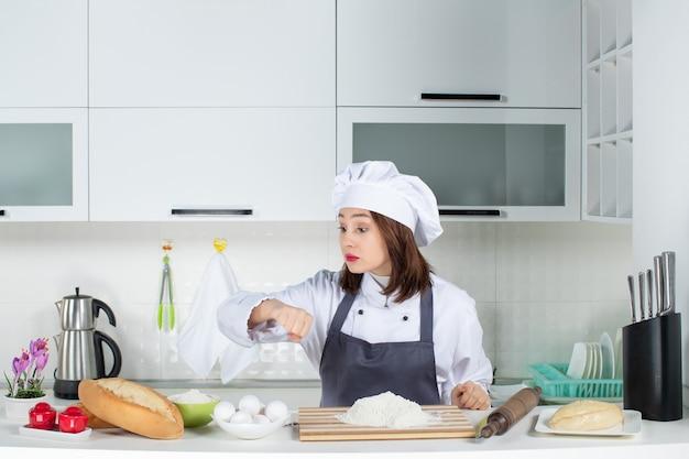 白いキッチンで彼女の時間をチェックする制服を着た若い女性シェフの正面図