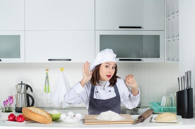 白いキッチンで最後のうわさ話を聞いている制服を着た若い女性シェフの正面図
