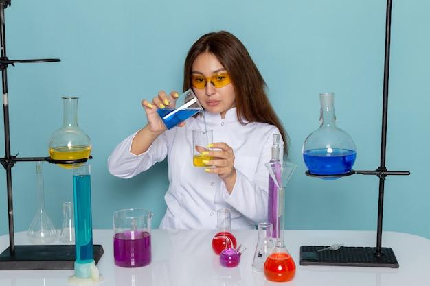 カラフルなソリューションを扱うテーブルの前に白いスーツの若い女性化学者の正面図