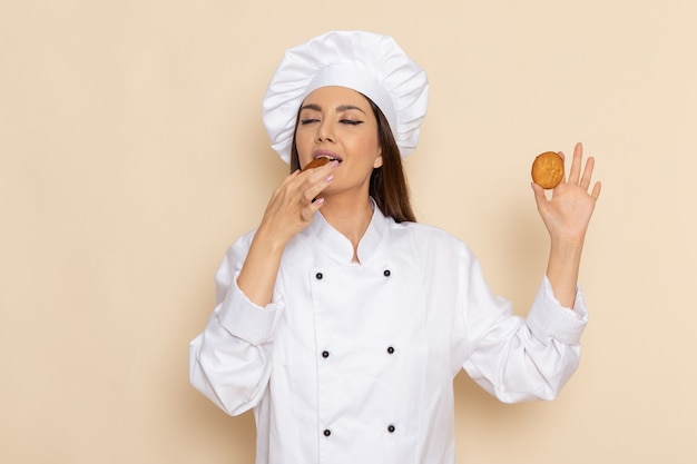 Вид спереди молодой женщины-повара в белом костюме повара ест печенье на белой стене