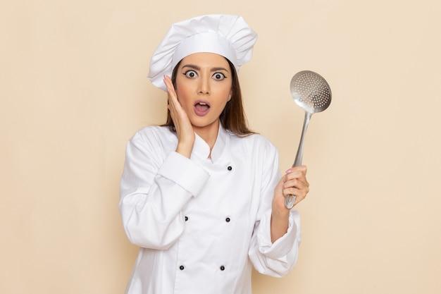 Вид спереди молодой женщины-повара в белом костюме повара, держащей большую серебряную ложку на светлой белой стене