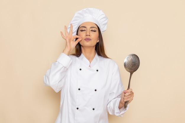 흰 벽에 큰 은색 숟가락을 들고 흰 쿡 정장에 젊은 여성 요리사의 전면보기