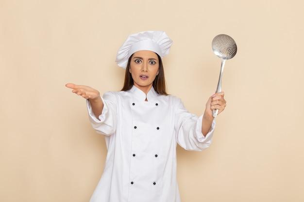 Вид спереди молодой женщины-повара в белом костюме повара, держащей большую серебряную ложку на белой стене