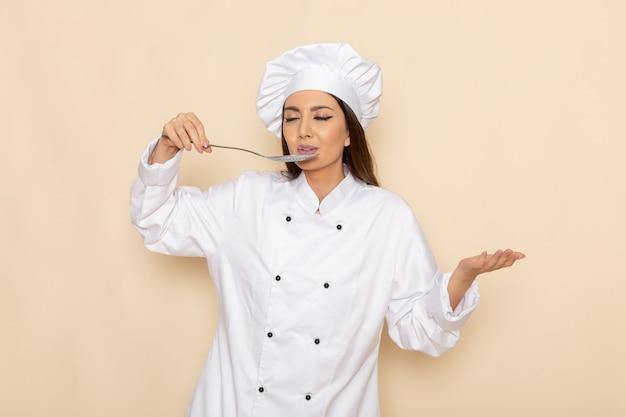 Вид спереди молодой женщины-повара в белом костюме повара, держащей большую серебряную ложку, дегустирующую ее на белой стене