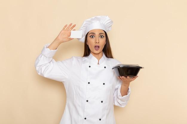明るい白い壁に黒いボウルとカードを保持している白いクックスーツの若い女性料理人の正面図