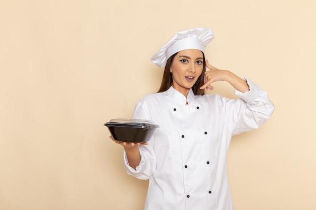 Вид спереди молодой женщины-повара в белом костюме повара, держащей черную сковороду на белой стене