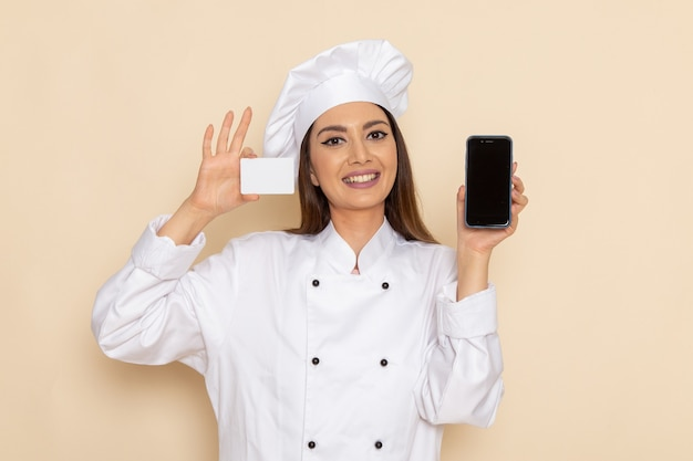 Вид спереди молодой женщины-повара в белом костюме повара, держащей карточку и телефон на светло-белой стене
