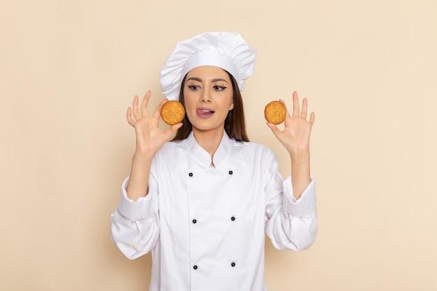 Вид спереди молодой женщины-повара в белом костюме повара с печеньем на светлой белой стене