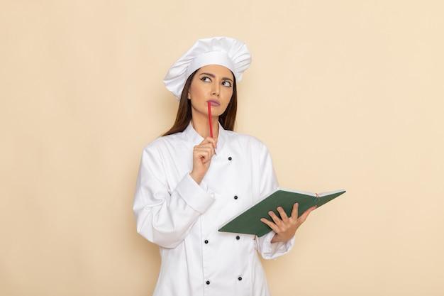 카피 북을 들고 밝은 흰색 벽에 생각하는 흰색 요리사 정장에 젊은 여성 요리사의 전면보기