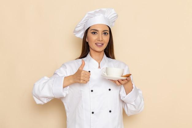 Вид спереди молодой женщины-повара в белом костюме повара, держащей чашку кофе и улыбающейся на белой стене
